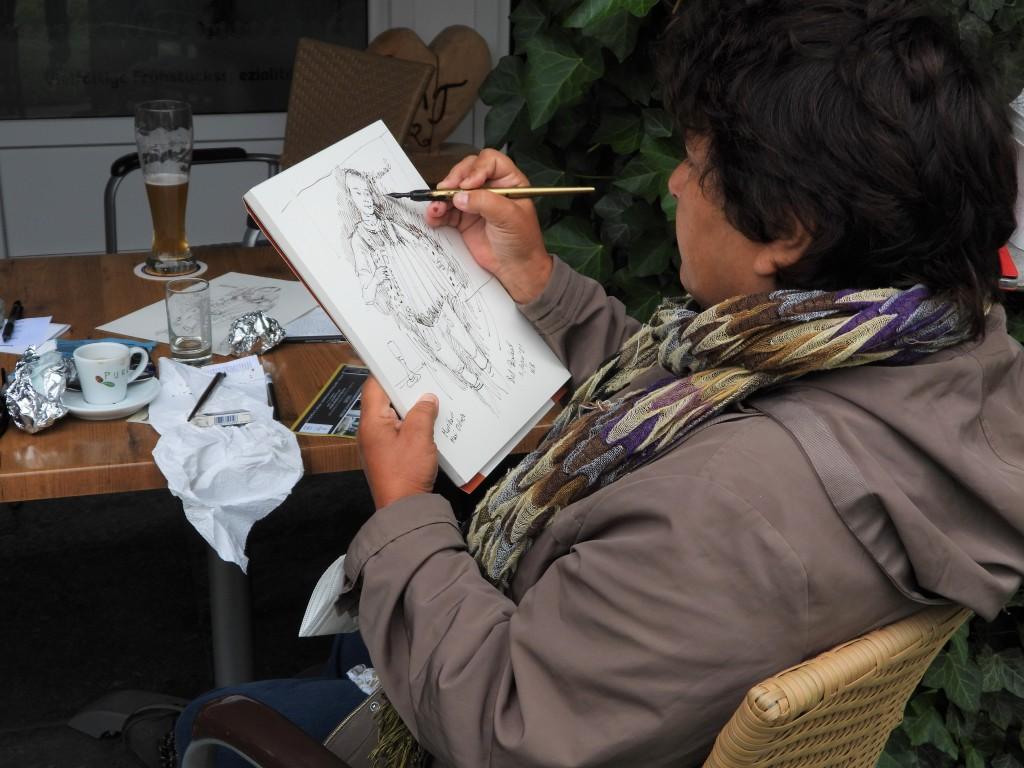 Künstlerin Nadia Baumgart beim zeichnen im Café